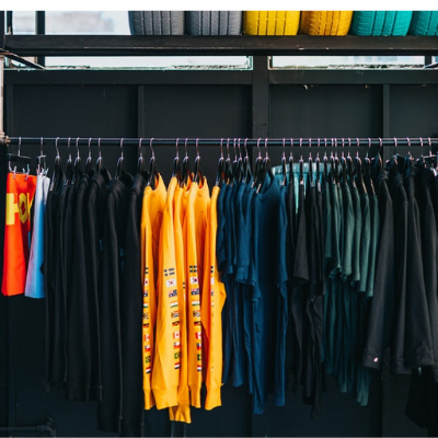 Assorted colour clothes on a rack below multi-coloured tyres. Ethical fashion is all about selecting the right fashion.