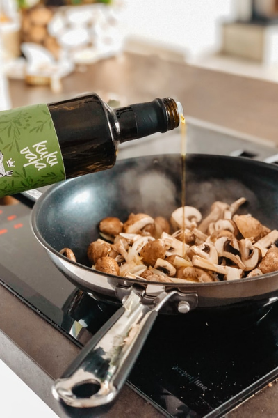 Oil being added to a pan of mushrooms on the stove