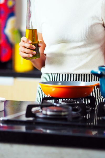 A person holding a bottle oil near a gas stove.