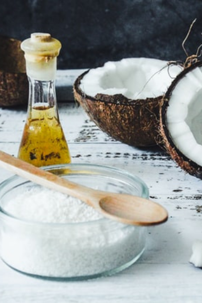 coconut oil in a jar, dessicated cocnut in a glass bowl, and an open coconut