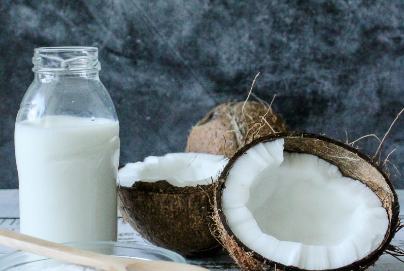 solid coconut oil in a jar, dessicated coconut in a glass bowl, and an open coconut